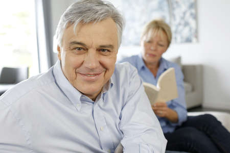 Smiling senior man sitting in couch, wife in background photo