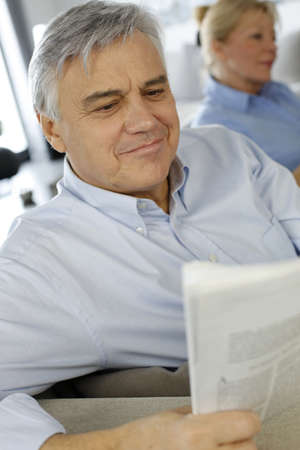 Senior man at home reading newspaper photo