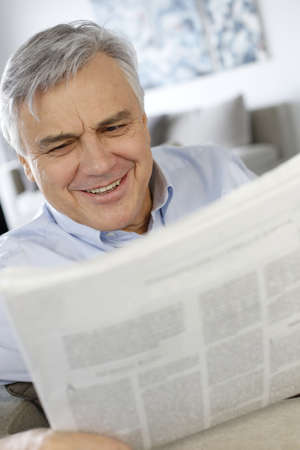Senior man smiling as reading the newspaper photo