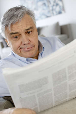 questioning: Senior man reading newspaper with puzzled look Stock Photo