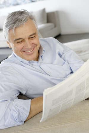 oude krant: Senior man glimlachend als het lezen van de krant Stockfoto