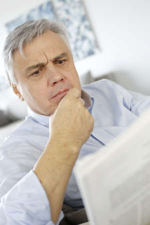 Senior man reading newspaper with puzzled look photo