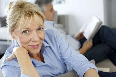 femme mari�e: Senior femme assise dans un canap?, le mari en arri?re-plan