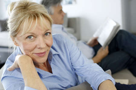 60 years old: Senior woman sitting in couch, husband in background Stock Photo