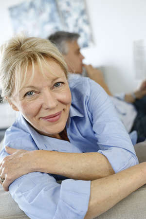 60 years: Senior woman sitting in couch, husband in background Stock Photo