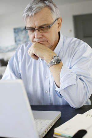 60 years: Senior businessman working from home on laptop Stock Photo