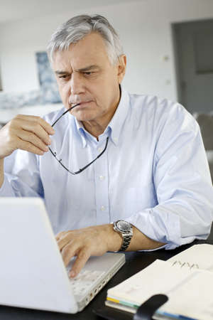 Senior businessman working from home on laptop Stock Photo - 16397561