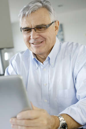 Senior businessman working on digital tablet from home photo
