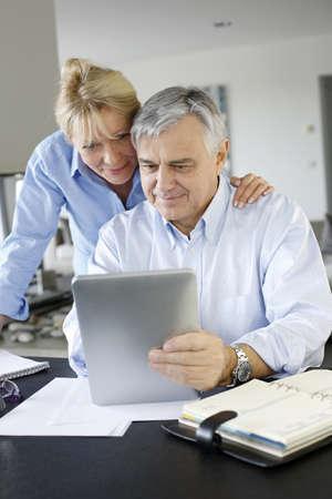 banking information: Senior couple looking at bank account on digital tablet