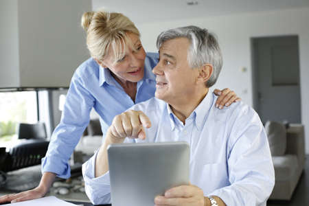inquiring: Senior couple looking at bank account on digital tablet