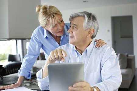 cuenta bancaria: Senior pareja mirando la cuenta bancaria en la tableta digital