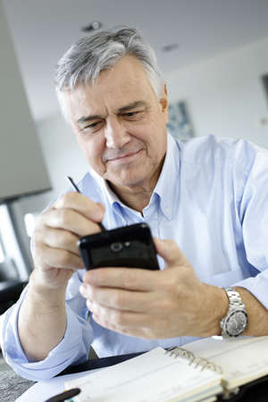 Portrait of senior businessman using smartphone photo