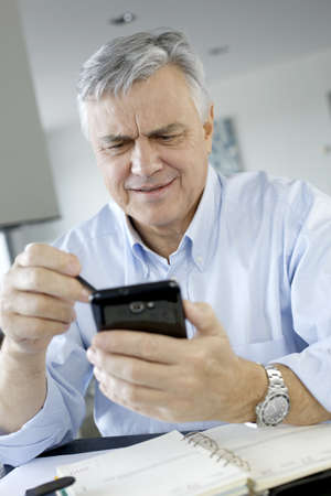telework: Portrait of senior businessman using smartphone