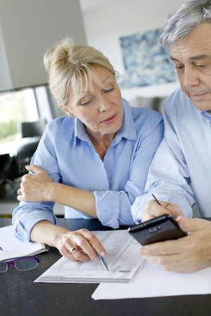 questioning: Senior couple calculting bills amount using smartphone