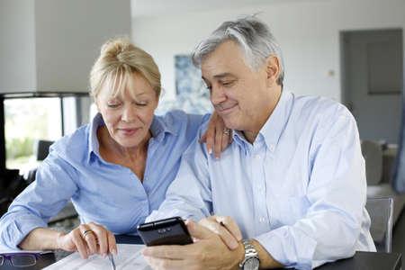 declaration: Senior couple calculting bills amount using smartphone