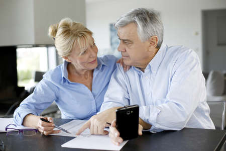 fill fill in: Senior couple calculting bills amount using smartphone