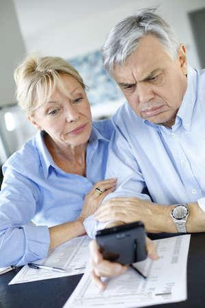 Senior couple calculting bills amount using smartphone Stock Photo - 16398580