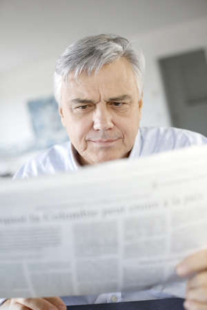 Senior businessman reading newspaper photo