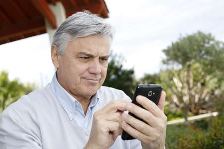 Senior man using smartphone in garden photo