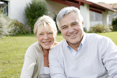 60 years old: Smiling senior couple sitting in garden