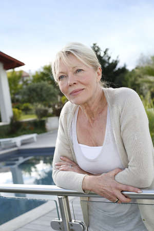 Portrait of senior woman standing in front of home Stock Photo - 16398626