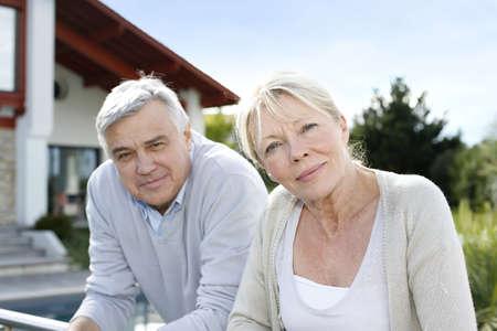 jubilados: Sonriente pareja de ancianos de pie en el jard�n de casa
