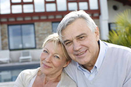 property owners: Smiling senior couple standing in home garden Stock Photo