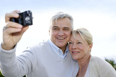 60 years old: Senior couple taking picture of themselves outside Stock Photo