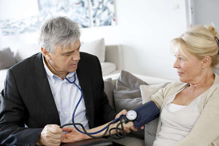 home visit: Doctor taking blood pressure to patient at home Stock Photo