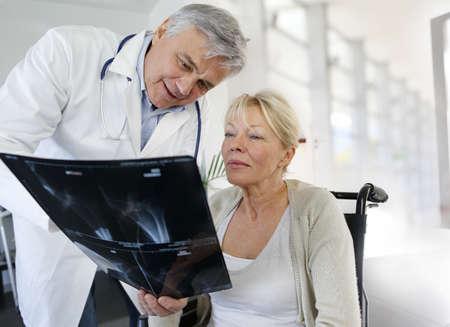 Cirujano de rayos X que muestra resultado a mujer en silla de ruedas