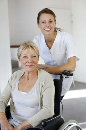 Nurse at home with elderly person in wheelchair photo