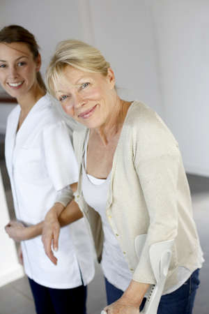 homecare: Nurse helping old woman to walk with crutches