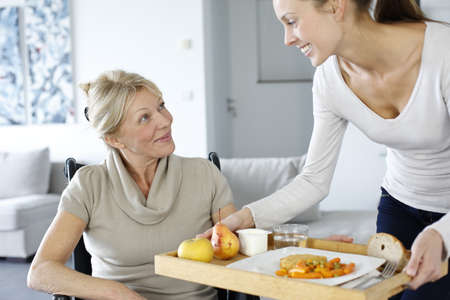 Young woman helping senior woman at home photo