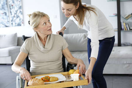 handicapped: Young woman helping senior woman at home