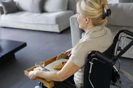 handicap: Senior donna in sedia a rotelle che tiene vassoio del pranzo