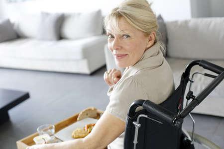 persona en silla de ruedas: Mujer mayor en silla de ruedas que sostiene la bandeja del almuerzo Foto de archivo