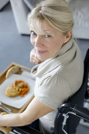 Senior woman in wheelchair holding lunch tray photo