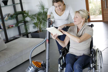home help: Young woman helping disabled lady at home Stock Photo