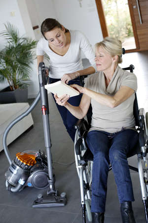 Young woman helping disabled lady at home photo