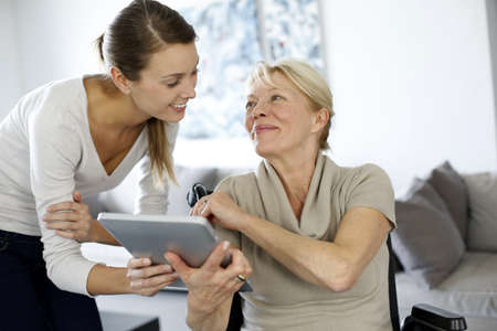 assistance: Girl showing tablet to elderly woman in wheelchair Stock Photo