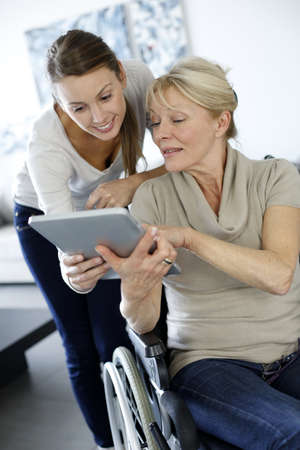 homecare: Girl showing tablet to elderly woman in wheelchair Stock Photo