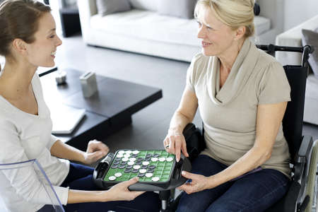 Young homecarer playing game with elderly woman photo
