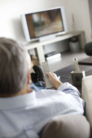 television remote: Back view of senior man in couch watching tv Stock Photo