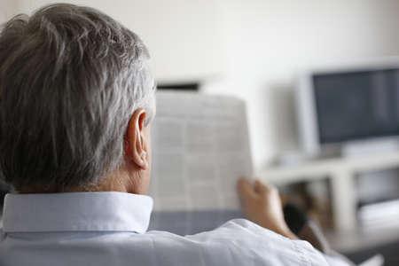 oude krant: Achteraanzicht van man lezing krant thuis