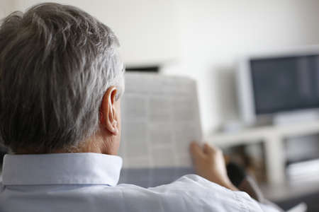 Back view of man reading newspaper at home photo