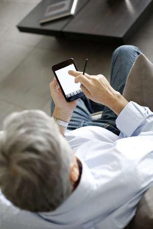 Back view of senior man using smartphone photo