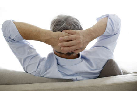 arms behind head: Back view of old man relaxing in sofa Stock Photo