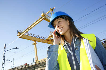 construction plans: Construction manager talking on mobile phone