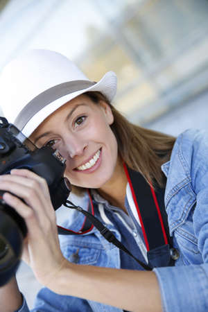 Portrait of smiling girl holding photo camera photo