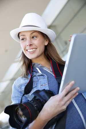 Smiling photographer using digital tablet photo